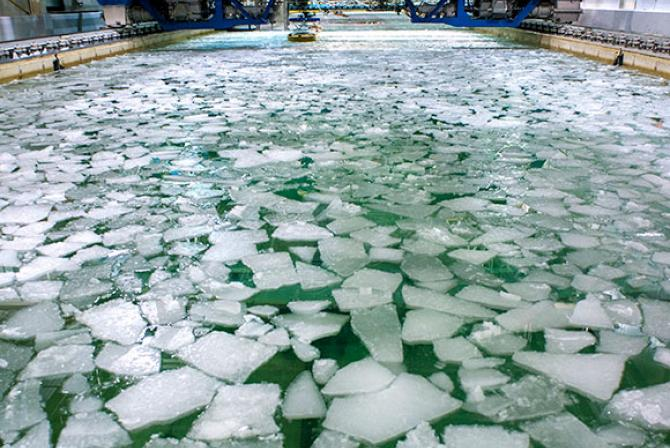Large rectangular indoor water tank with chunks of ice floating at the surface