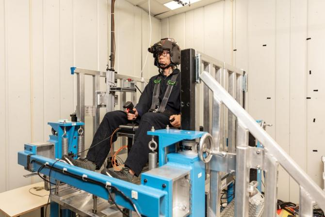 Human test subject wears monitoring equipment while seated on a metal structure