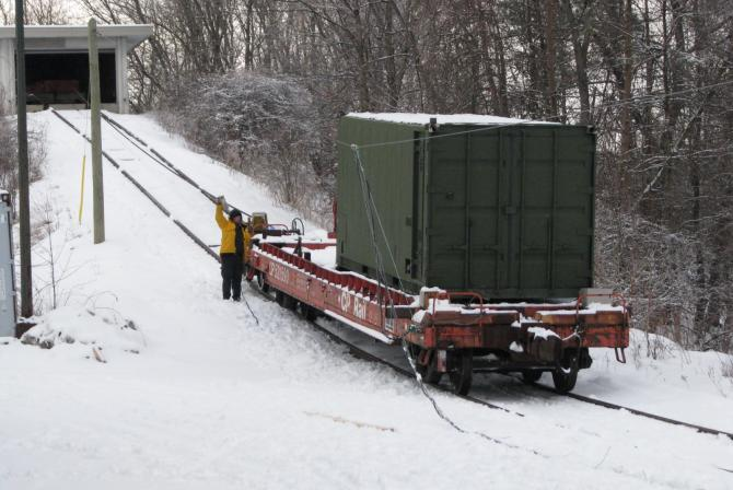A flatbed on rails at the base of a hill in winter