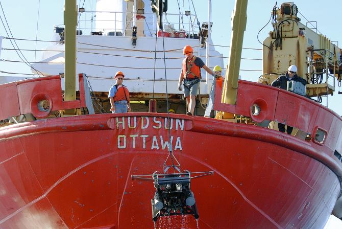 Equipment being maneuvered with a winch at the stern of a ship at sea