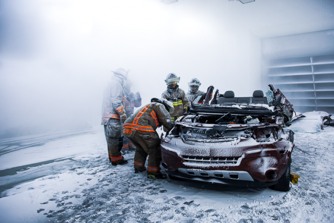 Team of firefighters work on a very damaged car in a snow covered chamber