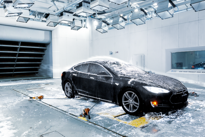 Winds and ice blown on black sports car in a test chamber