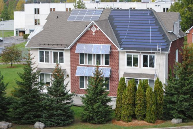 Aerial view of a multi-unit house with solar panels on the roof