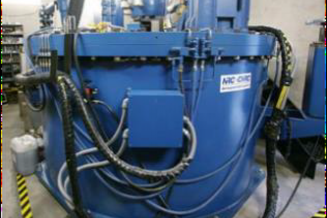 Exterior view of a large enclosed metallic cylindrical test rig with numerous heavy gage electrical cables attached to provide energy for internal heat