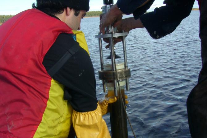 Persons collecting sediment cores from a lake