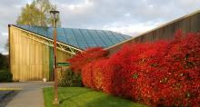 The entrance to a research facility with red bushes against the exterior wall