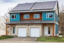 Front-exterior view of side-by-side semi-detached houses, with siding and stone veneer cladding, and solar panels on the roof.