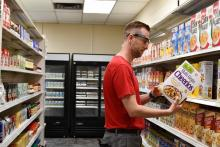 Person in a grocery aisle wears eyeglasses and examines the side of a Cheerios cereal box