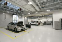 A bright, open garage space with two vehicle bays occupied by vehicles under inspection