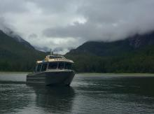 Boat on the water in front of mountains and a cloudy sky