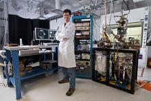 Researcher standing in a laboratory in front of microscopy instruments