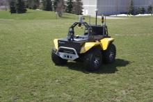 Robotic utility vehicle outdoors on grass